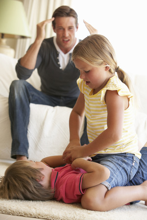 Enfants battre devant père à la maison Banque d'images