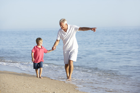 grandson: Grandfather And Grandson Enjoying Walk Along Beach