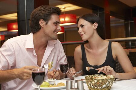 dining out: Young Couple Enjoying Meal In Restaurant Stock Photo