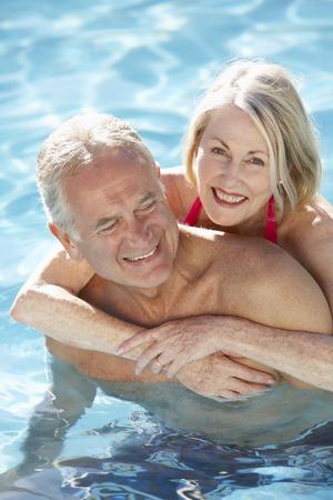 수석 커플 수영장에서 함께 편안한 휴식 스톡 콘텐츠