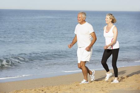 Hogere Paar joggen langs het strand Stockfoto