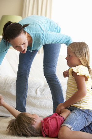 girl fighting: Children Fighting In Front Of Mother At Home Stock Photo
