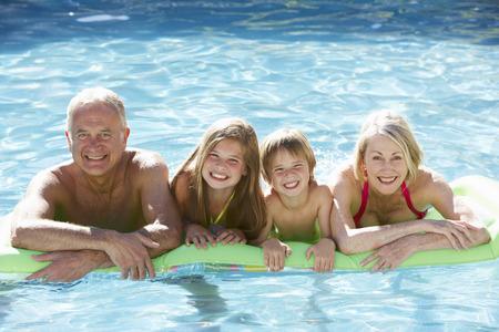 祖父母と孫が一緒にプールでリラックス 写真素材