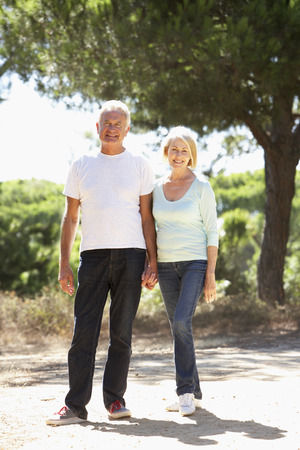 countryside loving: Senior Couple On Romantic Walk In Countryside Stock Photo