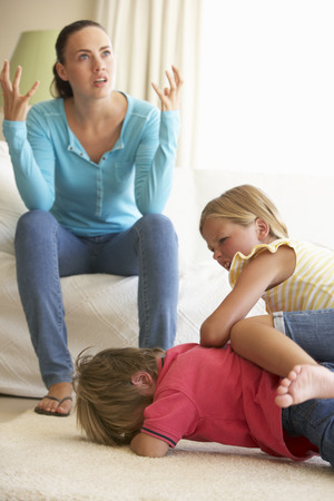 violent: Children Fighting In Front Of Mother At Home Stock Photo