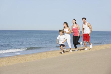 Retrato de familia en ejecución en vacaciones en la playa
