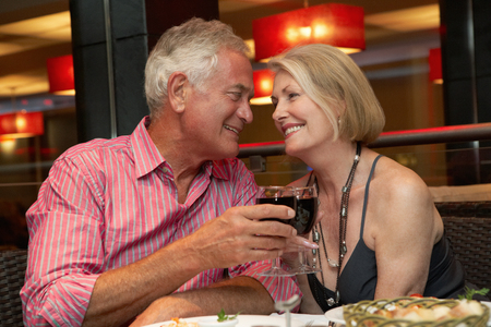 romantic evening with wine: Senior Couple Enjoying Meal In Restaurant Stock Photo