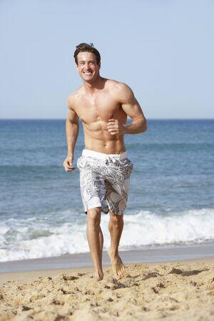 fitness hombres: Hombre joven que desgasta el traje de natación ejecuta a lo largo de la playa
