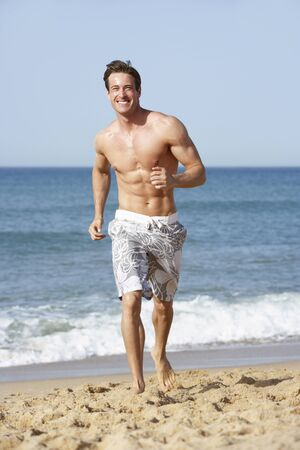swimming costume: Young Man Wearing Swimming Costume Running Along Beach