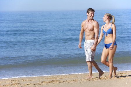 chase: Young Couple Walking Along Summer Beach Stock Photo