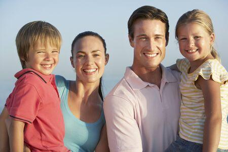madre e figlio: Portrait Of Young Family On Beach Holiday Archivio Fotografico