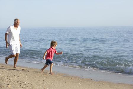 abuelo: Abuelo y nieto correr a lo largo de la playa