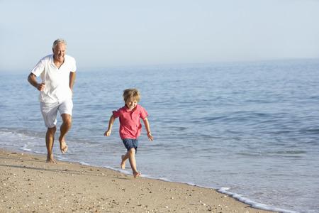 persona de la tercera edad: Abuelo y nieto correr a lo largo de la playa