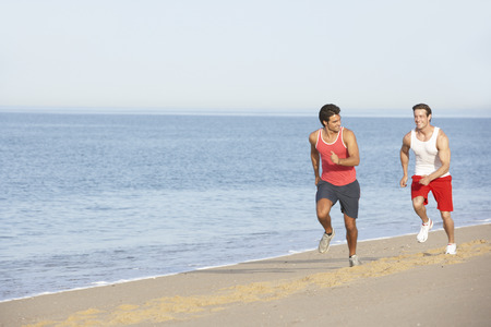 gente corriendo: Dos hombres jóvenes correr a lo largo de la playa