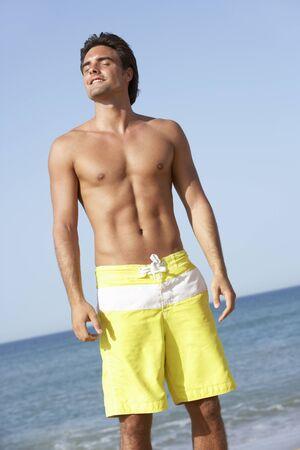 swimming costume: Young Man Wearing Swimming Costume Standing On Beach