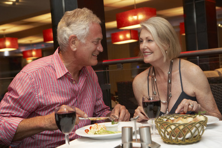 dining out: Senior Couple Enjoying Meal In Restaurant Stock Photo