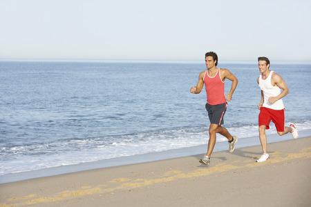 jog: Two Young Men Jogging Along Beach