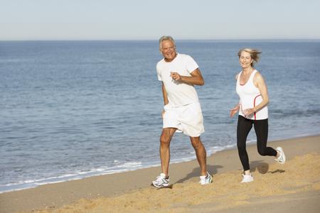 jogging: Senior Couple Jogging Along Beach