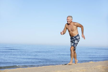 Senior Man Running Along Summer Beach Stock Photo