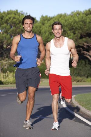 hombres corriendo: Dos hombres que se ejecutan en la carretera Foto de archivo