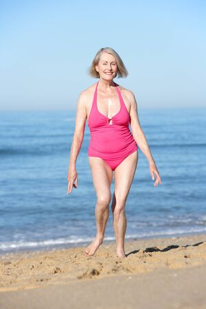 senior women: Senior Woman Running Along Summer Beach