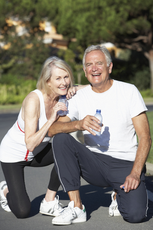couple exercising: Senior Couple Resting And Drinking Water After Exercise