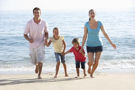 sandy beaches: Running Family On Beach Holiday Stock Photo