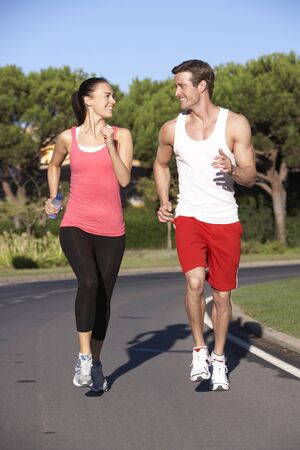 jogging track: Young Couple Running On Road Stock Photo
