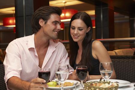 tomando vino: Pares jovenes que disfrutan de la comida en restaurante