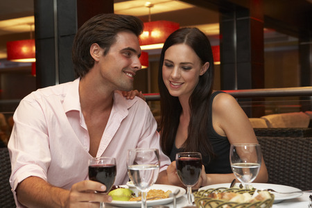 food and wine: Young Couple Enjoying Meal In Restaurant Stock Photo