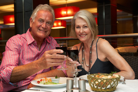 senior eating: Senior Couple Enjoying Meal In Restaurant Stock Photo