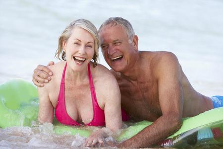 couple having fun: Senior Couple Having Fun In Sea On Airbed