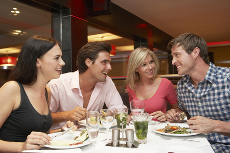 dining out: Group Of Young Friends Enjoying Meal In Restaurant