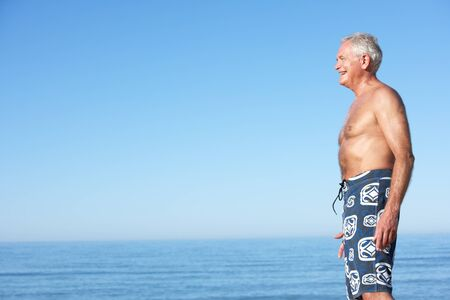 swimshorts: Senior Man Standing On Summer Beach Stock Photo