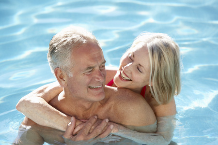 older couple: Senior Couple Relaxing In Swimming Pool Together