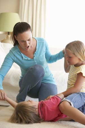 Children Fighting In Front Of Mother At Home Stock Photo