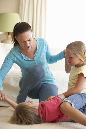 personas discutiendo: Niños que luchan delante de la madre en el hogar