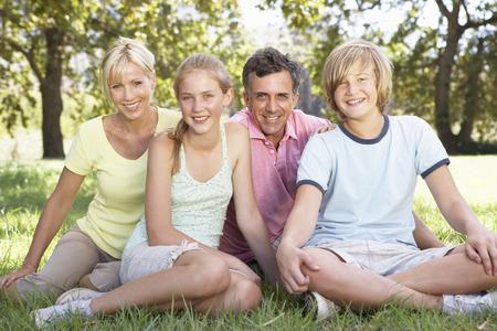 中年の家族は田舎でフィールドに座って 写真素材