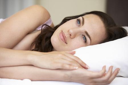 mujer en la cama: Mujer joven relajante en cama