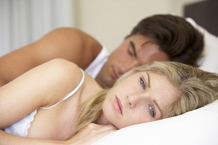 pareja en la cama: Preocupado Pareja joven en la cama