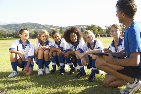 coach sport: Group Of Children In Soccer Team Having Training With Coach