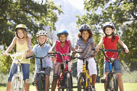 niños en bicicleta: Grupo de niños que montan las bicis en Campo Foto de archivo