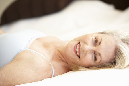 70s adult: Senior Woman Relaxing On Bed Stock Photo