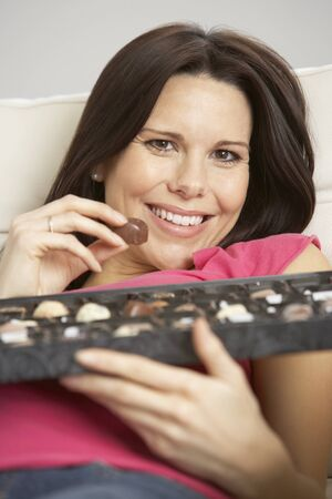 craving: Pregnant Woman Eating Box Of Chocolates Sitting On Sofa At Home Stock Photo