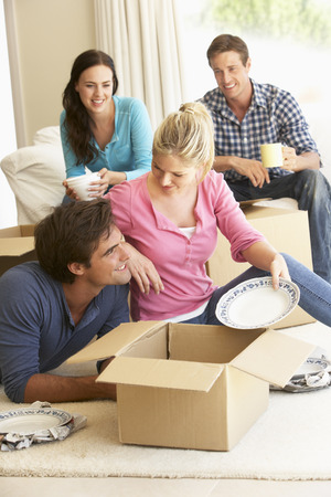 unpacking: Friends Moving Into New Home Unpacking Boxes Stock Photo