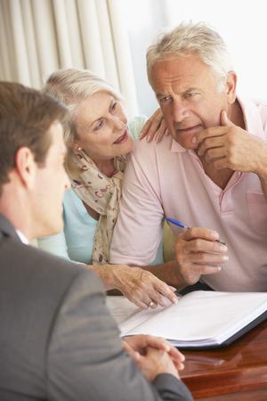 Senior paar ontmoeting met financieel adviseur thuis zoek Bezorgd