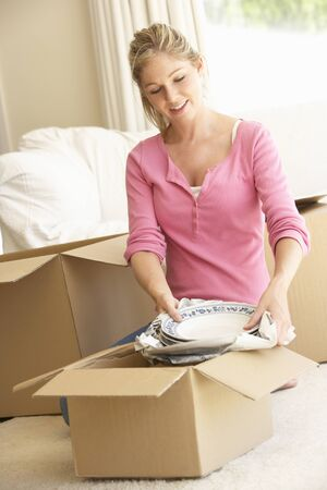 unpacking: Young Woman Moving Into New Home Unpacking Boxes Stock Photo