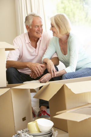 Senior Couple Moving Home And Packing Boxes Stock Photo