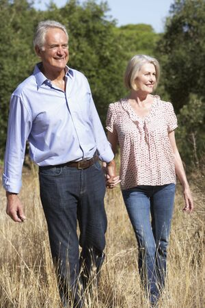 countryside loving: Senior Couple Walking Through Summer Countryside Stock Photo