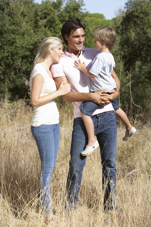 three year old: Young Family Walking Through Summer Countryside
